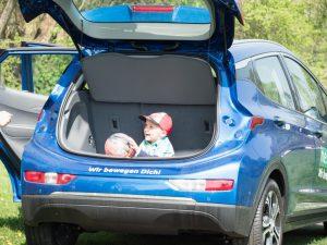 Opel Ampera-e in blau mit offenem Kofferraum und Kind